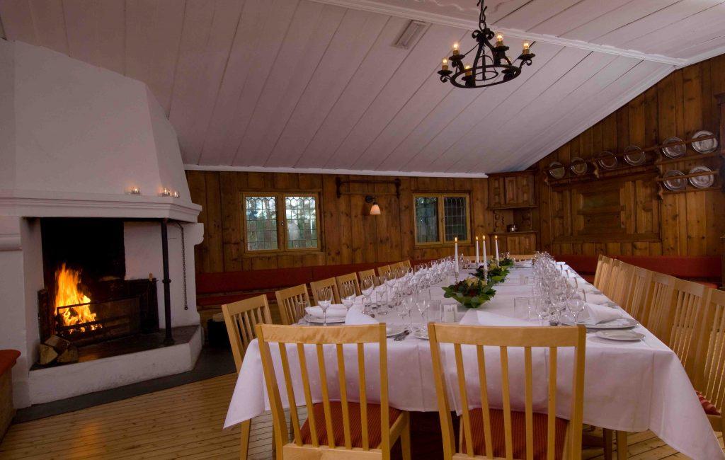 Festlokaler på Gjestestuene med peisbål og dekket bord